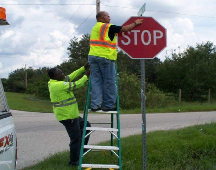 two men installing a stop sign at an intersection