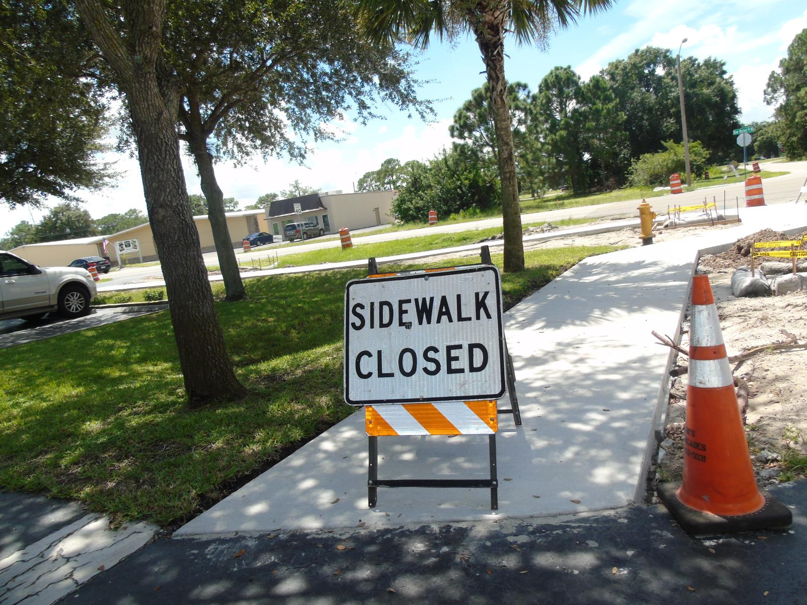 Sidewalk being repaired with a sidewalk close sign